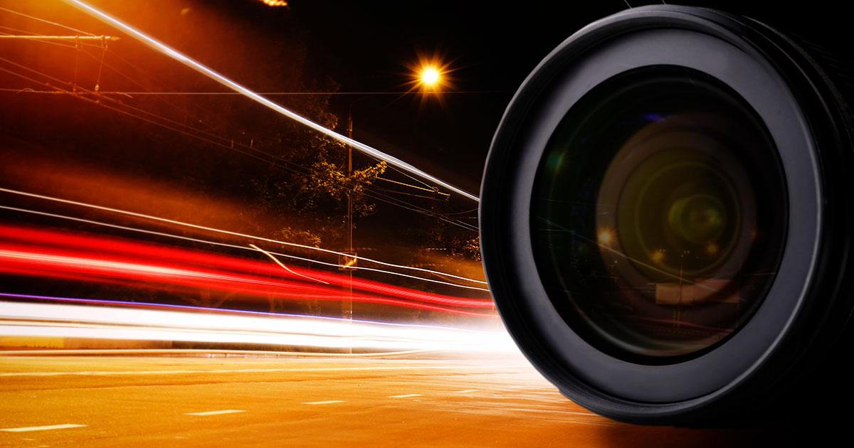 Kamera ja öinen tie valoissa.