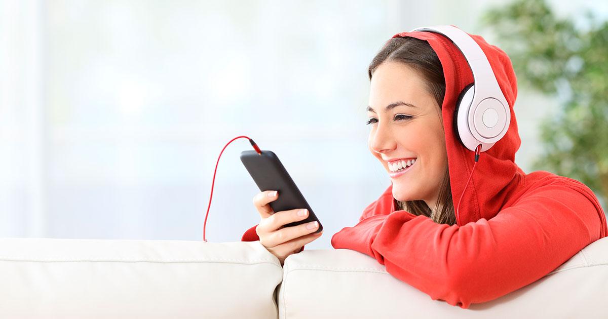 Nainen käyttää kännykkää ja kuuntelee kuulokkeilla.