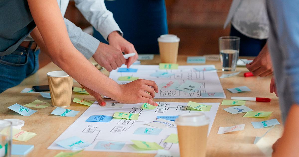 Henkilöt tekevät kaaviota pöydän ääressä.