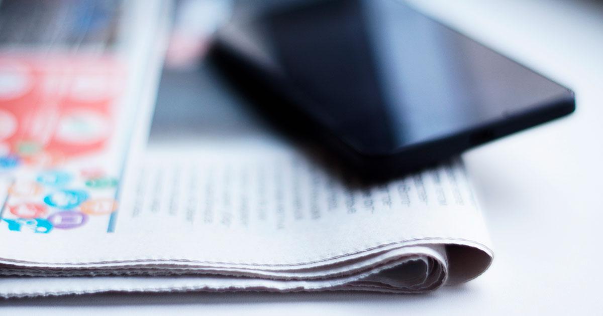 Sanomalehti ja kännykkä pöydällä.