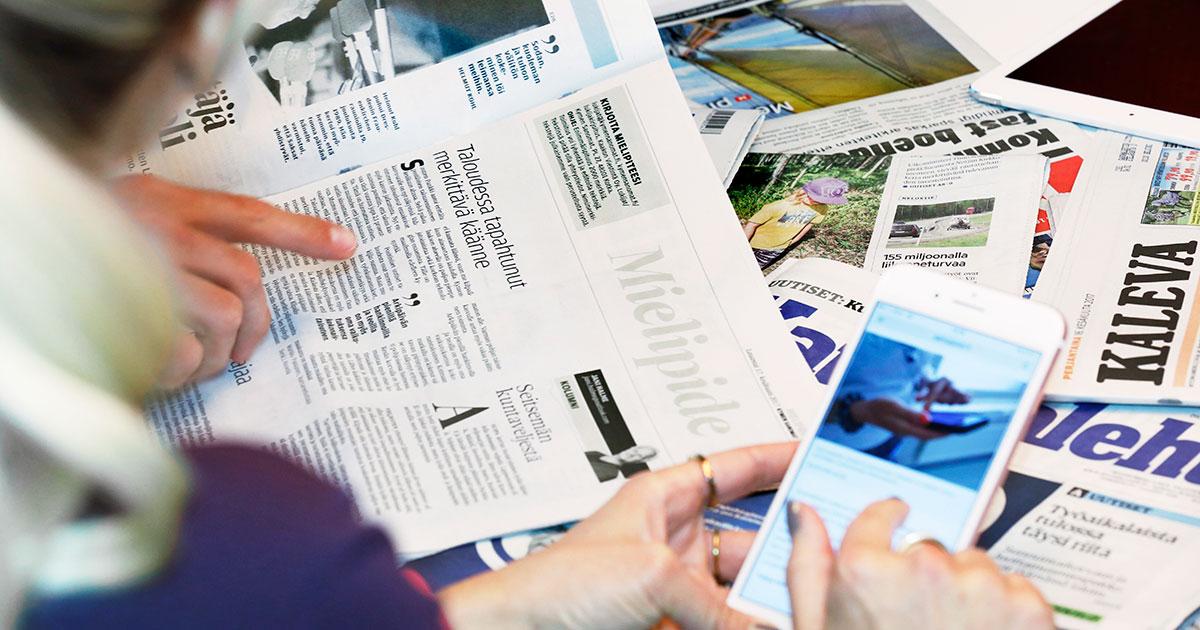 Sanomalehtiä ja kännykkä pöydällä.