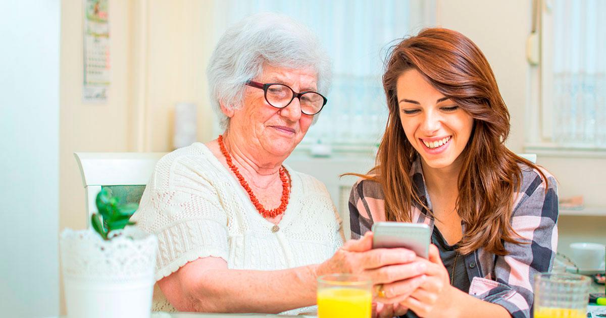 Seniori ja nuorempi henkilö lukevat uutisia älypuhelimella.